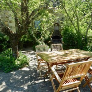 Die Terrasse des Ferienhauses Bergerie mit Tisch, Stühle und Grill