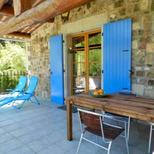 The upper terrace of cottage Clède in front of the front door with outside table, chairs and deck chairs