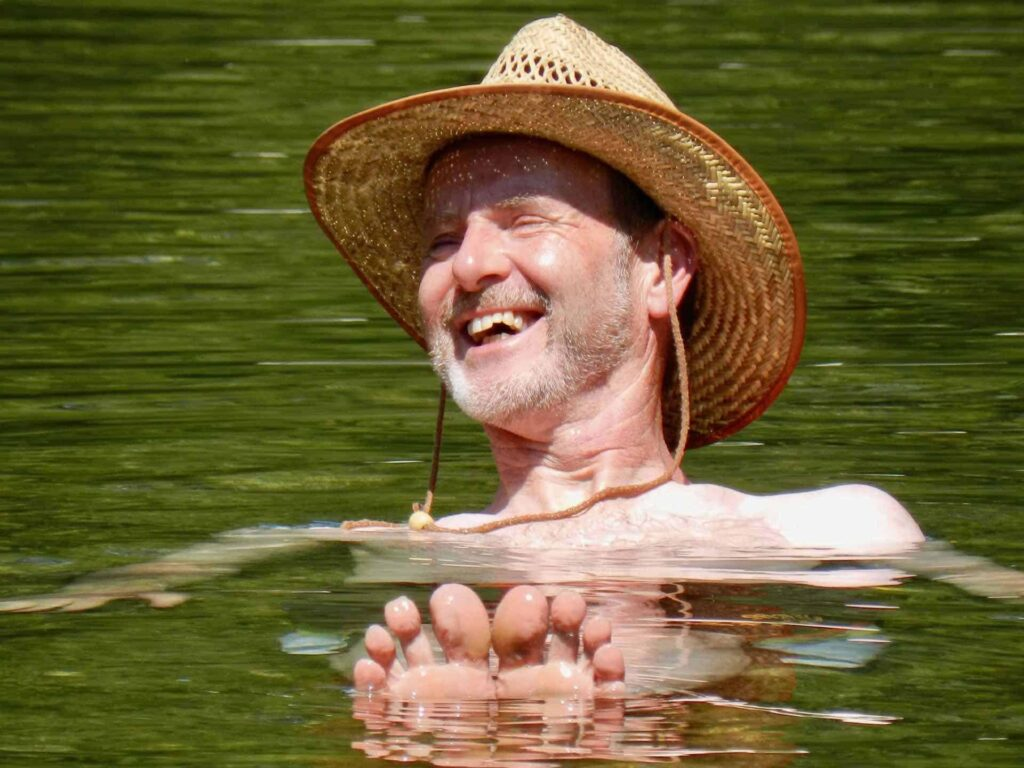 A smiling man floating in the river