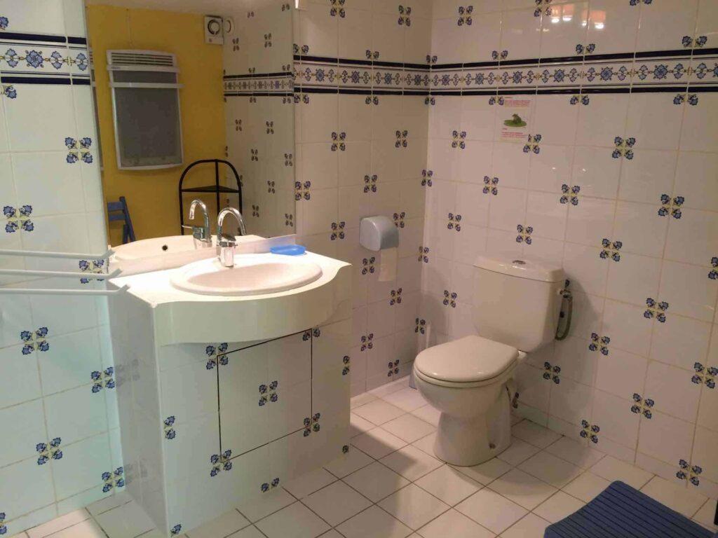 Ein Teil des Badezimmers des Ferienhauses Gîte du Moulin mit Waschbecken und Toilette