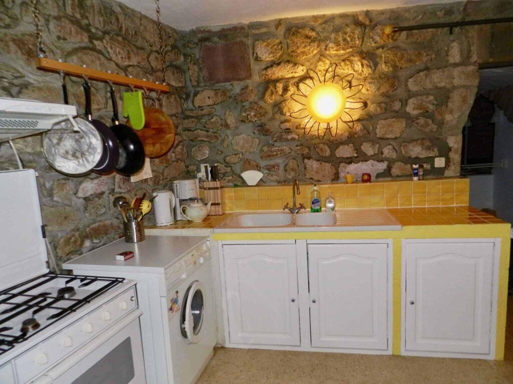 Die Küche vom Ferienhaus Gîte du Moulin mit Waschbecken, Gasherd und Waschmaschine