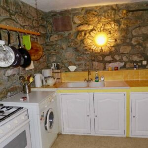The kitchen of holiday cottage Gîte du Moulin with gas cooker, washing machine, sink and cupboards