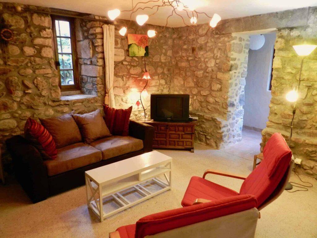 Das Wohnzimmer vom Ferienhaus Gîte du Moulin mit Sofa, Stühle und Tisch.