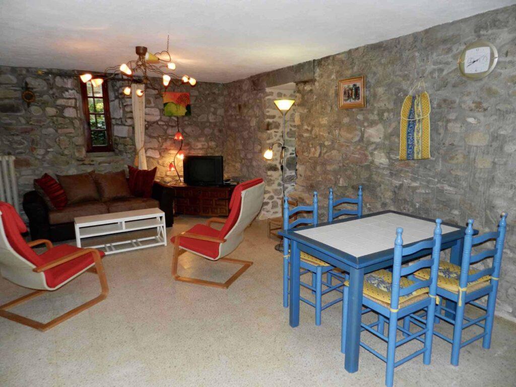Das Wohnzimmer des Ferienhauses Gîte du Moulin mit dem Küchentisch