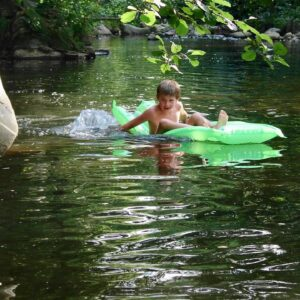 Child on airbed in river