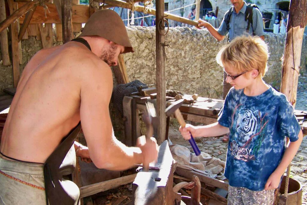 A boy with a hammer helps a medieval smith form an arrow point.
