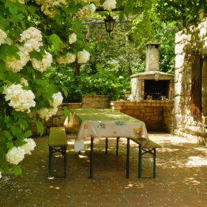 The terrace of the cottage Orangerie with outside table, benches and barbecue