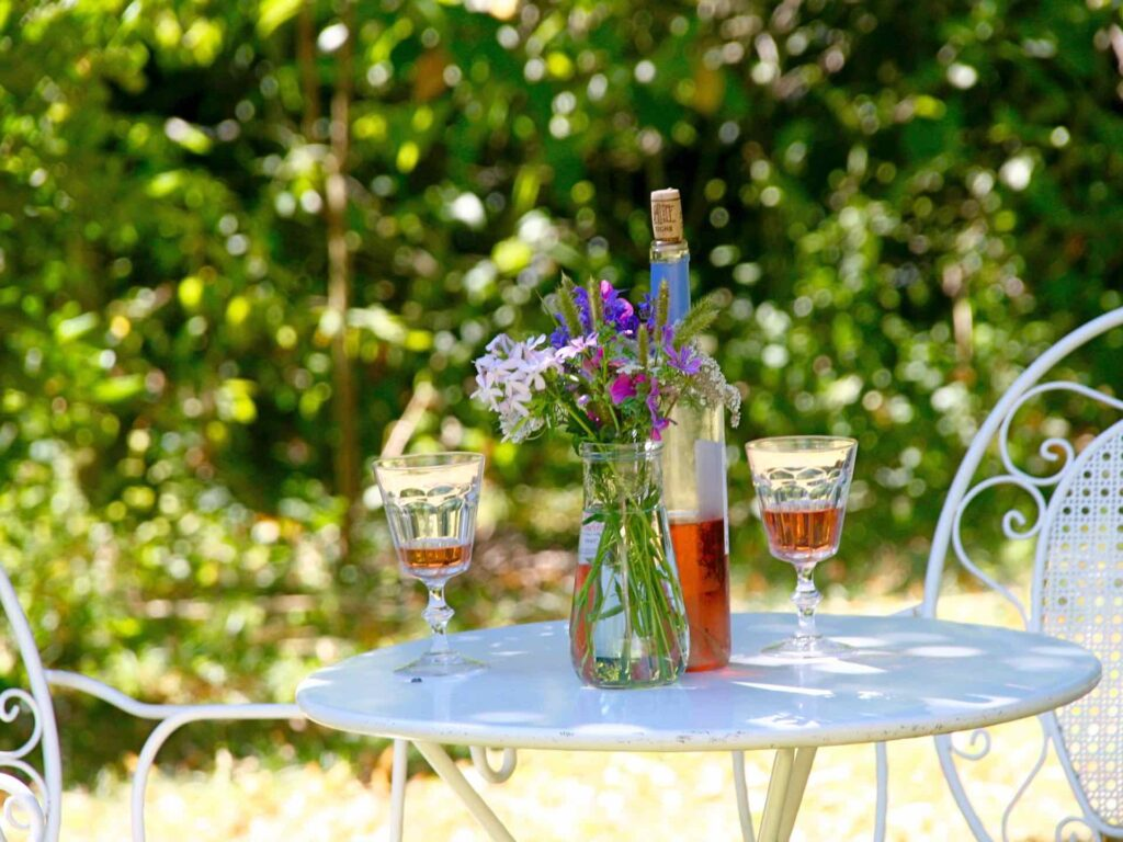A bottle of wine, two glasses and flowers on a sunny garden table