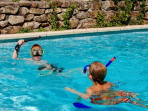 Two boys with dive masks play in the swimming pool