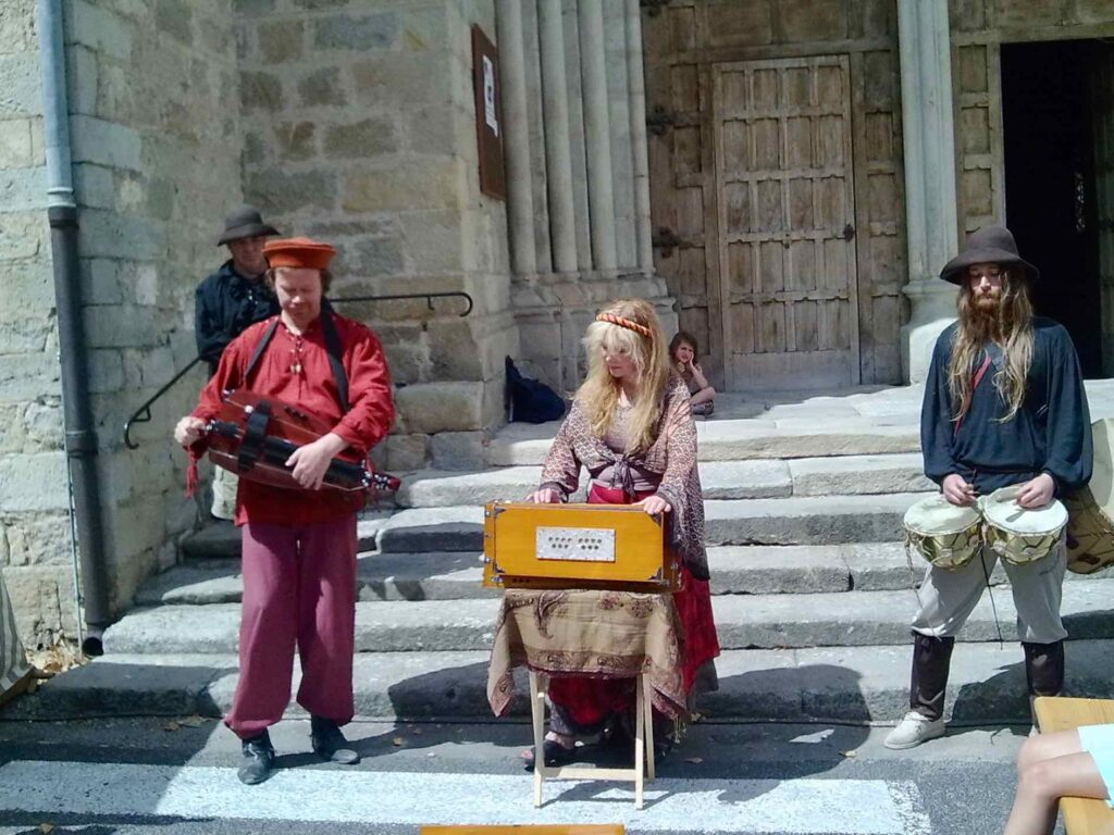 Medieval musicians play in front of the church in Largentière.